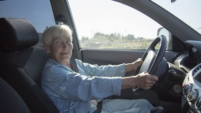 an smiling elderly woman driving car