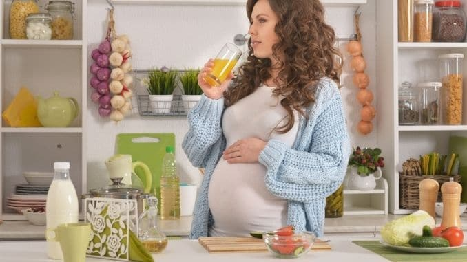 Pregnant young woman having breakfast