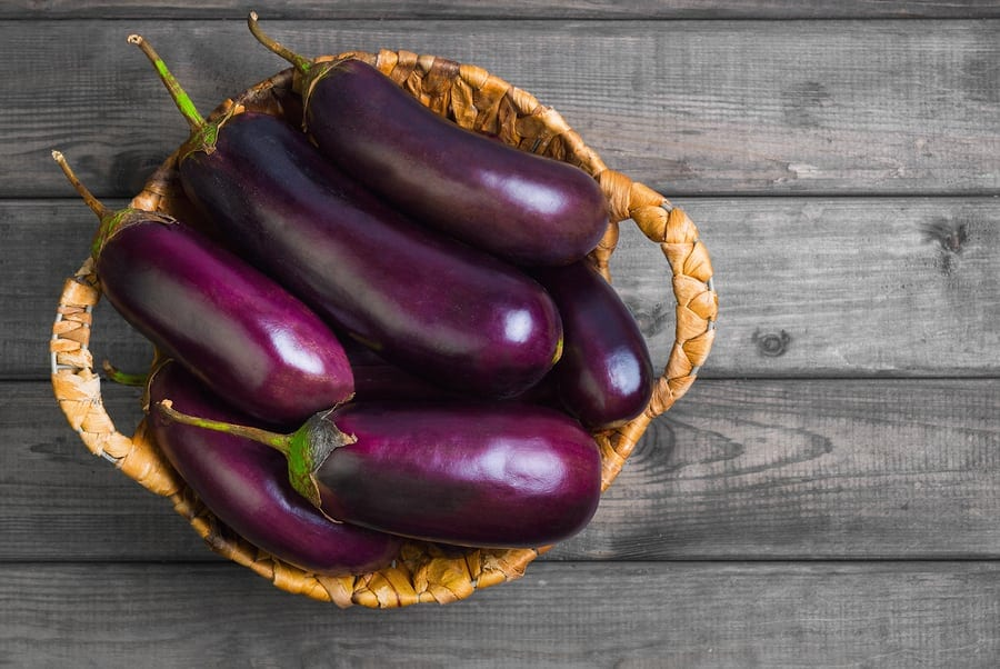 Fresh raw Purple Eggplant in a special wicker basket for Eggplant on gray wooden background. Top view blank space.