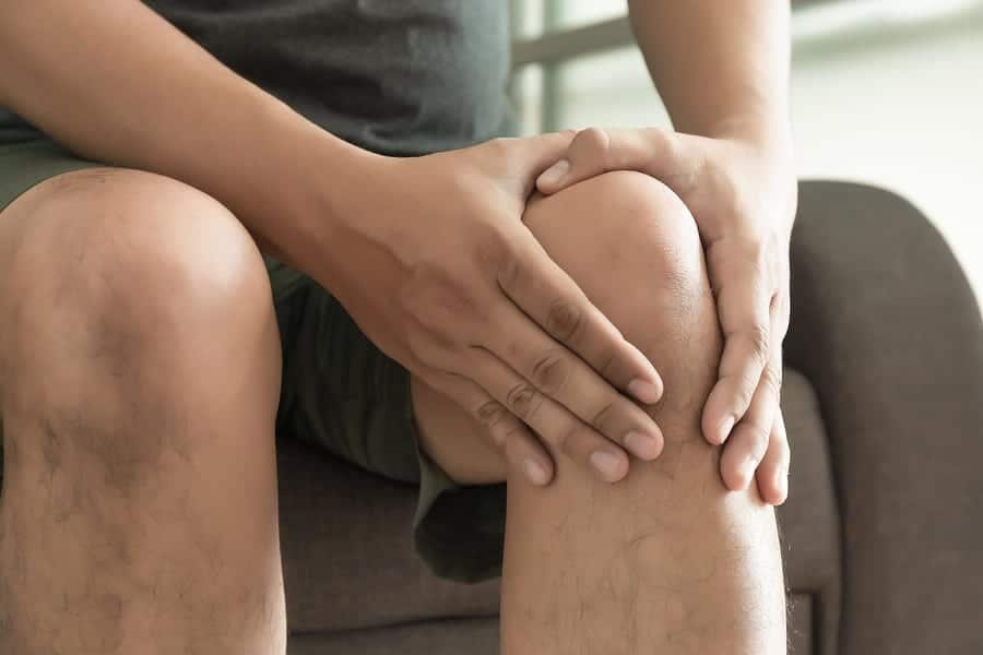 The Knee Man Holds On Suffering From Pain In Knee Closeup. The L