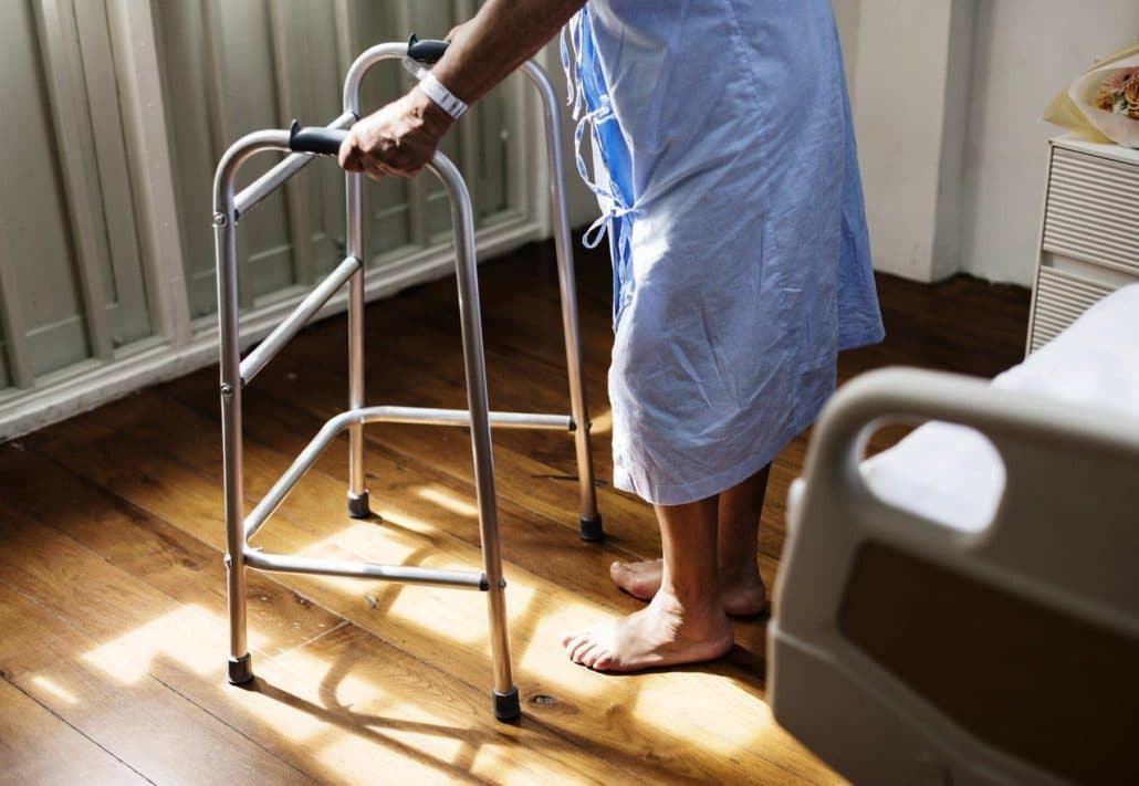 person-in-hospital-gown-using-walking-frame
