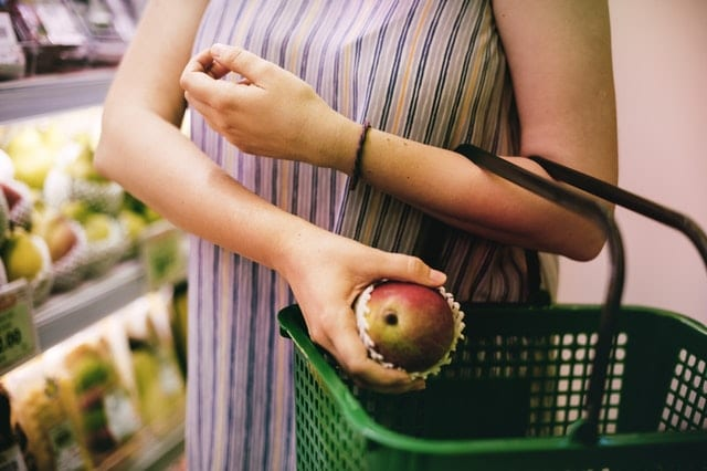 woman-putting-red-apple-on-green-shopping-basket