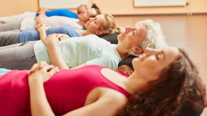 Group-of-people-with-senior-making-breathing-exercise