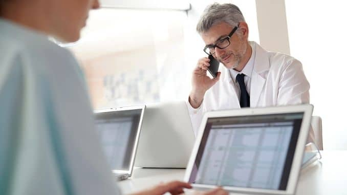 doctor in office talking on phone