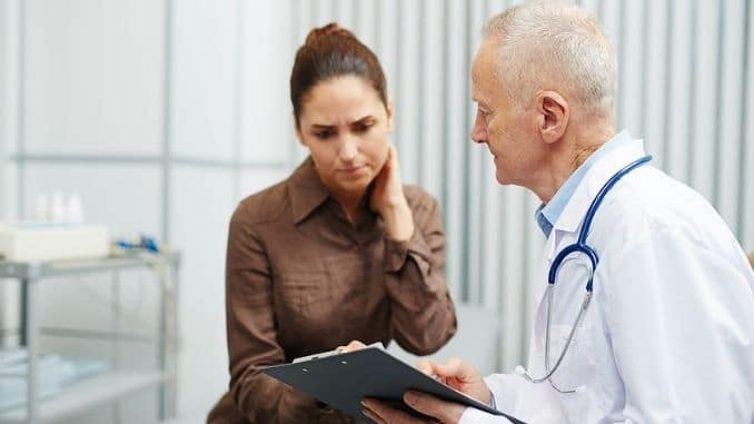 Sad nervous young woman touching neck while reading her medical