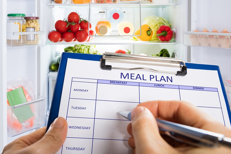 Persons Hand Filling Meal Plan Form On Clipboard