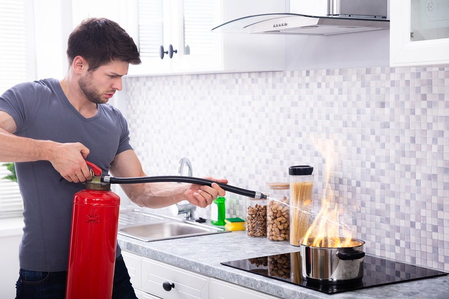Man Using Fire Extinguisher To Stop Fire On Burning Cooking Pot