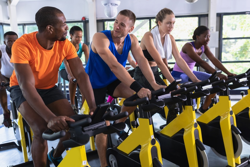Front view of diverse fit people exercising on exercise bike in fitness center. Bright modern gym with fit healthy people working out and training at spin class