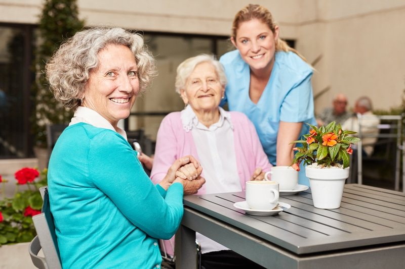 Senior citizen drinks coffee with visit and caregiver