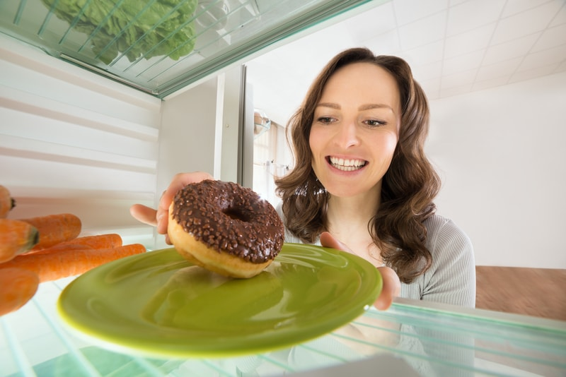 Woman Taking Chocolate Donut From Refrigerator