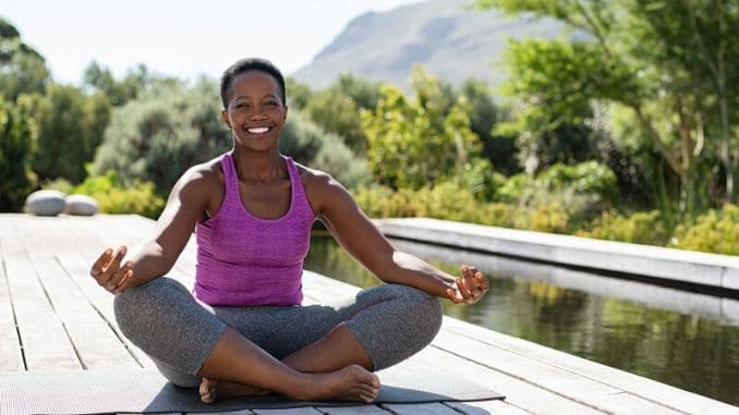 Mature african woman in yoga lotus position
