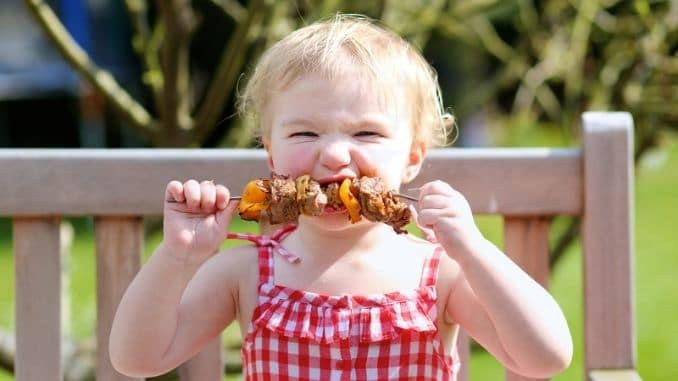 girl eating grilled meat